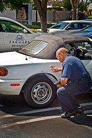 An adjuster evaluates damage to a car for an insurance claim. Note laptop and insurance company car in background.
