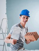 Young tradesman holding a trowel and a brick