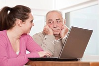 Young woman explaining the computer to an elderly man