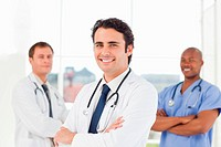 Smiling male doctors with their arms crossed standing in front of a window