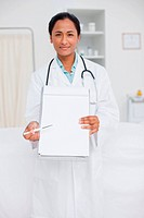 Young smiling doctor looking at the camera while pointing her clipboard