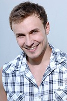 Young man smiling, wearing a check shirt, portrait