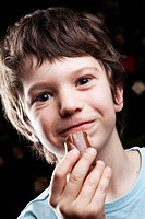 Boy eating chocolate and smiling