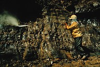 An environmental worker cleans oiled rocks with a high_pressure water spray, four months after the spill of May, 1969. Santa Barbara, California. The ...