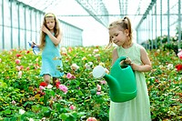 An image of two girls in a greenhouse