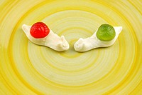 Two marshmallow snails on a plate, candy