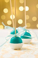 Turquoise Christmas cake pops sticking upside down in miniature cupcake liners. Very shallow depth of field with Christmas lights in the background