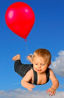 A little boy wearing a farmer´s outfit and floating in the sky with a red balloon.
