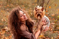 woman with curls and a little dog in nature, fall