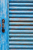 Door handles with an old wood door painted with blue