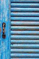 Door handles with an old wood door painted with blue