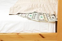 Paper currency underneath pillow case with bed frame and mattress as background