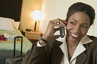 Businesswoman talking on phone in hotel room