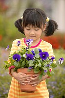 Girl holding pot of flowers