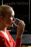 Woman drinking water in cafe