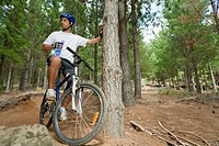 Mountain biker drinking water in forest