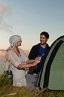 Couple setting up tent on hillside