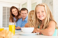 Smiling girl sitting at breakfast table