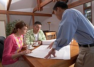 Man going over house plans with couple