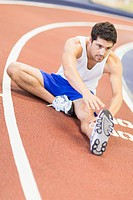 Man stretching on indoor track in gym