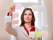 Businesswoman hanging up sticky notes