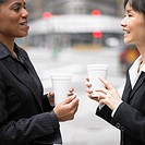 Businesswomen talking while drinking coffee