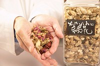 Chinese medicinal herbs in jar and cupped hands