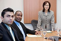 Businesswoman standing at conference table