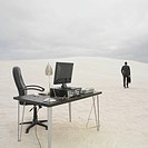Businessman walking away from desk in the desert