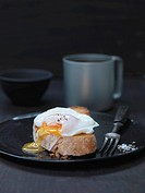 Free Range Organic Poached Eggwith oozing yolk on toast witha mug of coffee in the background and a fork by the toast
