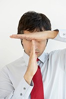Businessman making the time out symbol in front of his face