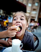 Girl eating in an outdoor café
