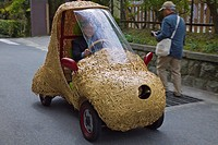 A man driving a car with a body of woven bamboo strips