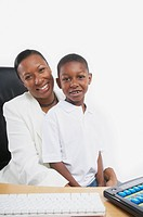 African businesswoman sitting at her desk with her young son