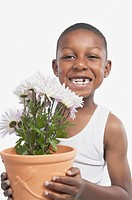 Studio shot of young African boy holding a potted plant