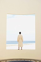 Person in robe looking out over the ocean