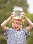 Young boy looking at frog in glass jar outdoors