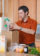 Man unpacking groceries in kitchen