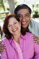 Middle_aged Hispanic couple hugging and smiling outdoors