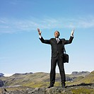 Businessman smiling with hand raised in deserted rural area