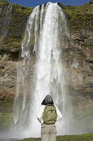 Woman wearing backpack and looking at waterfall