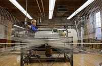 Amana, Iowa - A worker runs a warping creel at the Amana Woolen Mill  The machine gathers up to 240 strands of yarn that will later be woven into clot...