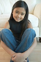 Asian girl sitting on floor smiling