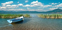 wide view of a row boat and cloudscape on lake Prespa from the macedonian side