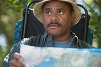 African man with map and backpack in woods