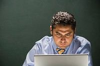 Hispanic businessman using laptop
