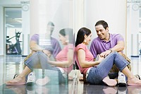 Hispanic couple sitting on floor