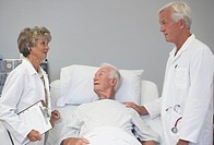Male and female doctors talking with senior male patient in hospital bed