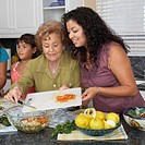 Multi_generational Hispanic female family members preparing food