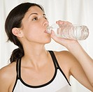 Hispanic woman drinking bottled water
